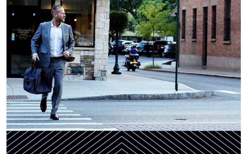 a sharply dressed man crossing the street