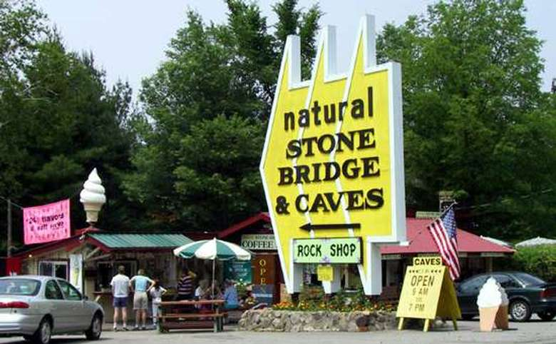 Sign outfront of the caves with people in the background getting ice cream