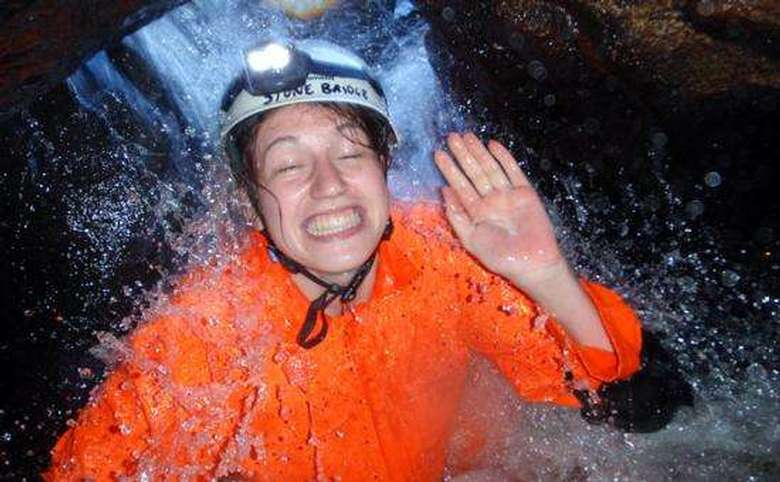 Woman getting drenched in water in cave