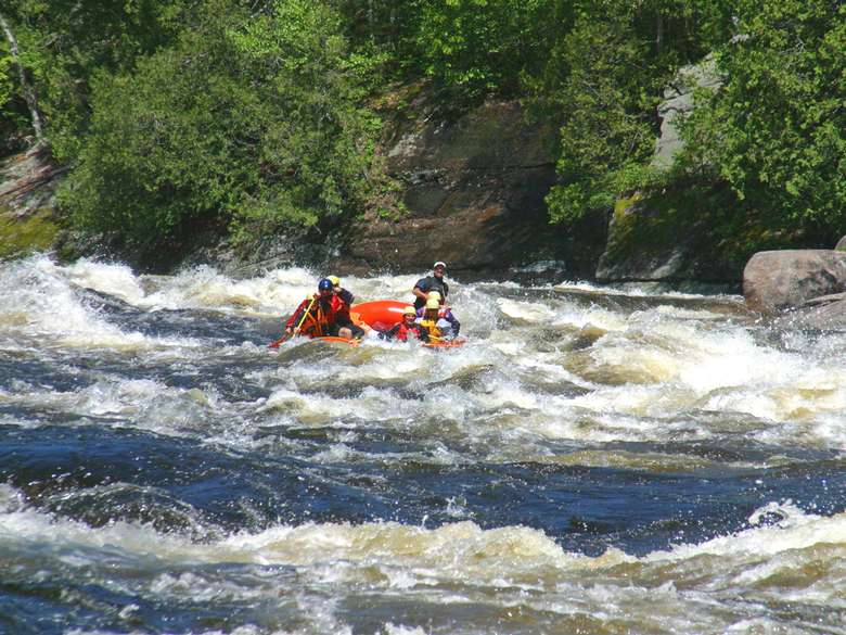 group of people whitewater rafting in an orange raft through a stretch of rapids