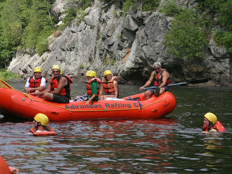 five people in an orange raft and two people in orange life jackets swimming in the water