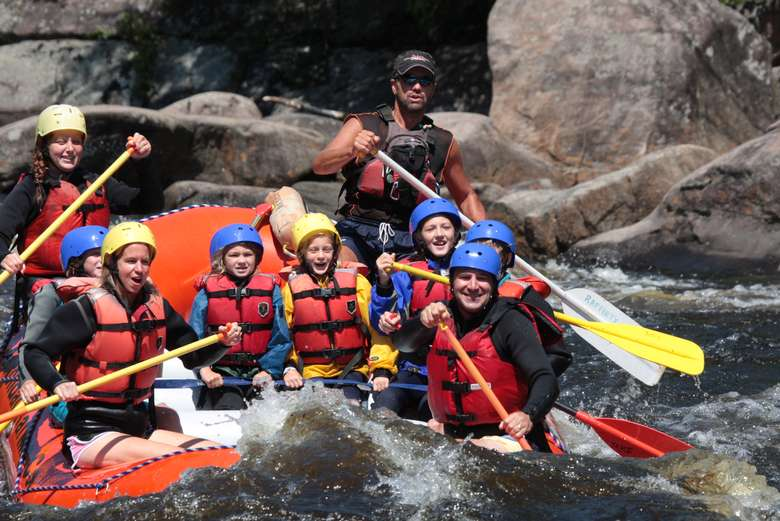 group of people whitewater rafting in an orange raft