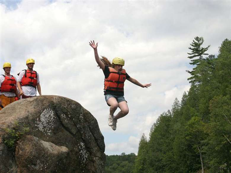girl in an orange lifejacket and yellow helmet jumping off a rock into the water