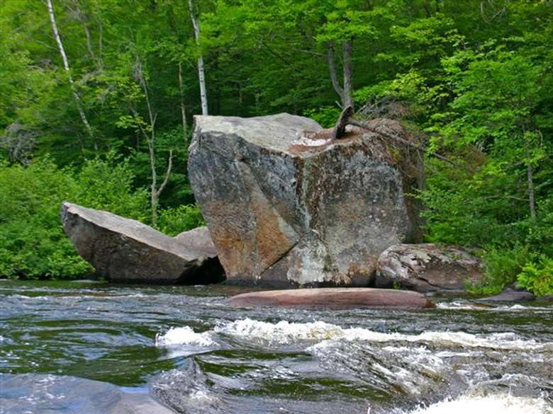 a large rock jutting out into a river