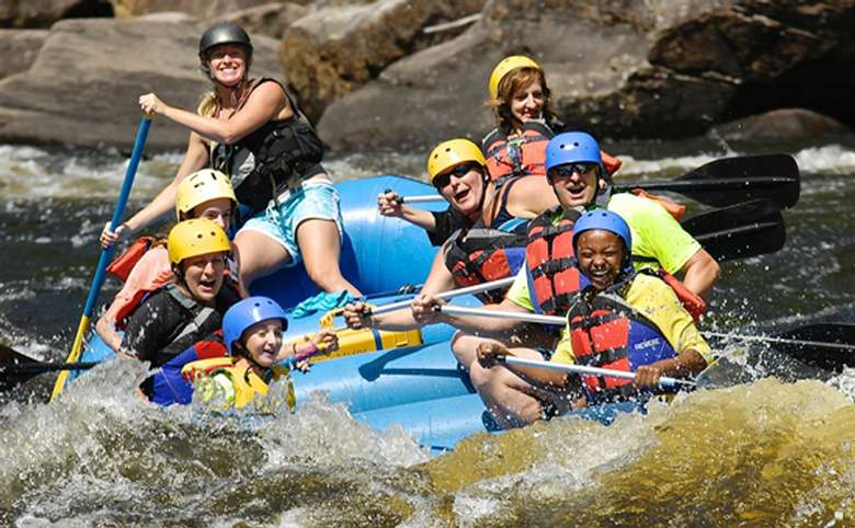 group of people whitewater rafting on a blue raft