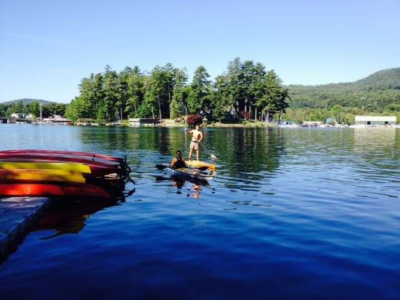 row of kayaks on a dock overlooking lake george while people kayak and paddleboard in the distance