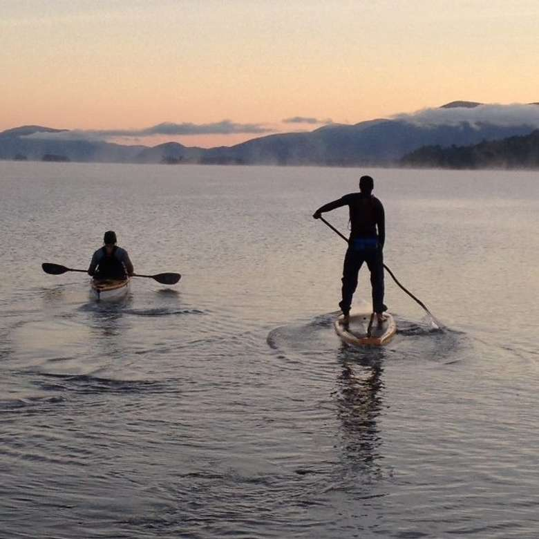 man stand up paddleboarding next to another man kayaking