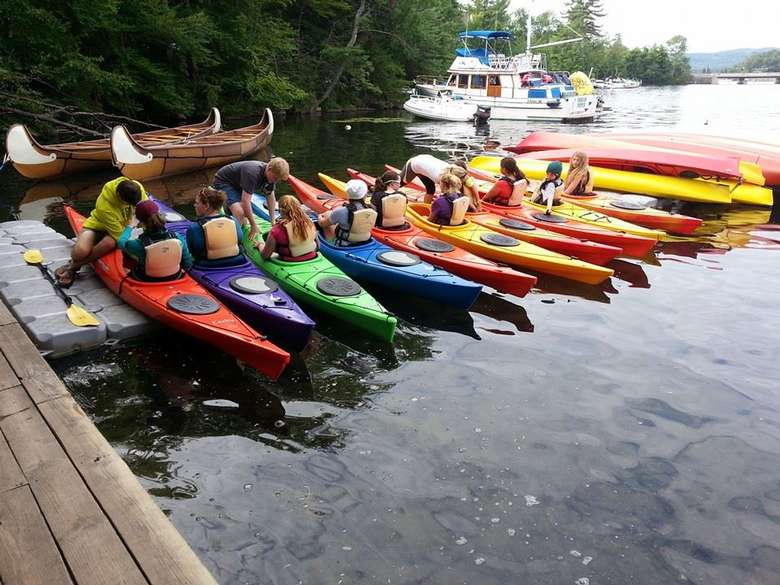 people in a rainbow of kayaks getting instruction before launching