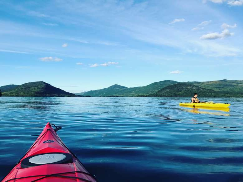 bow of a red kayak in lake george with another yellow kayak in the distance