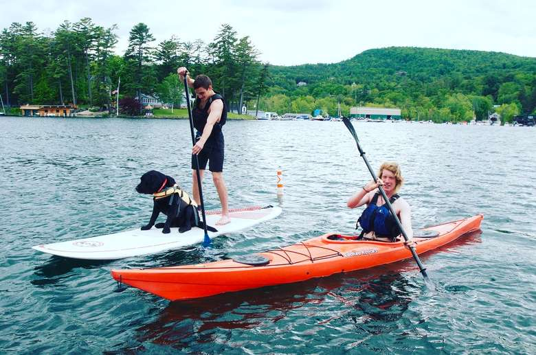 one person paddleboarding with a dog while another person kayaks alongside