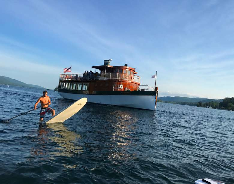 man stand up paddle boarding in front of a large boat