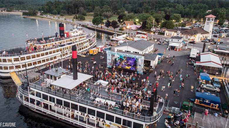 aerial view of rock the dock music festival on a pier surrounded by three large steamboats