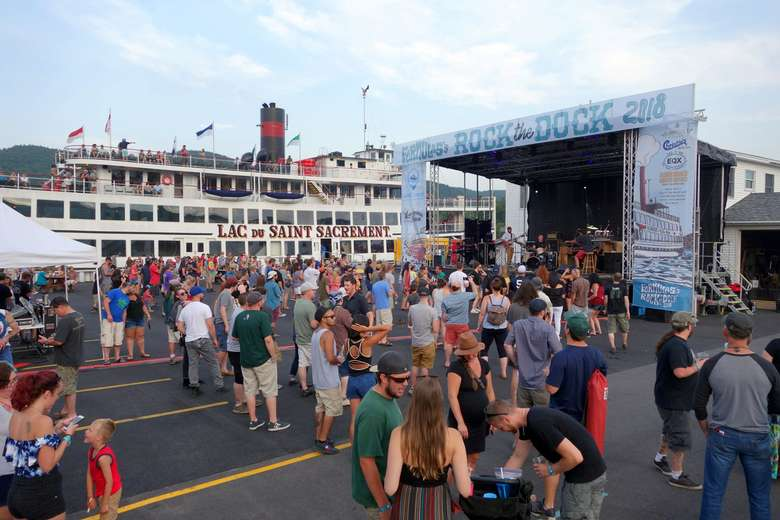 crowd of people at rock the dock music festival with large steamboat in the background