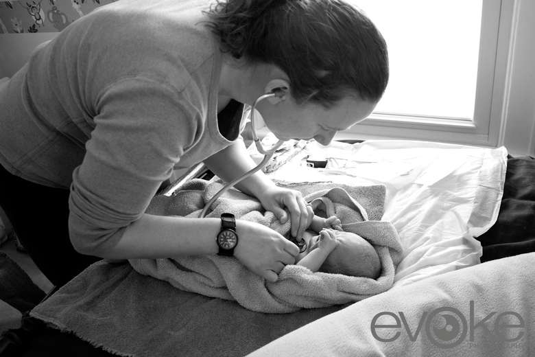 midwife checking on a newborn baby