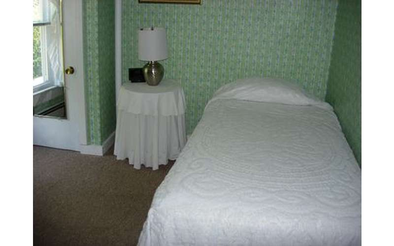 a small lamp on a table near a bed covered in white blankets