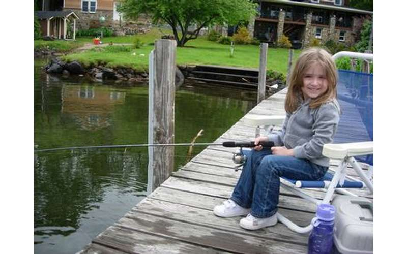 a girl with a fishing rod on a dock