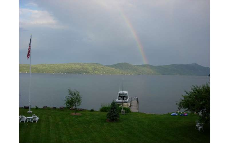 a rainbow in the distance over mountains and a lake