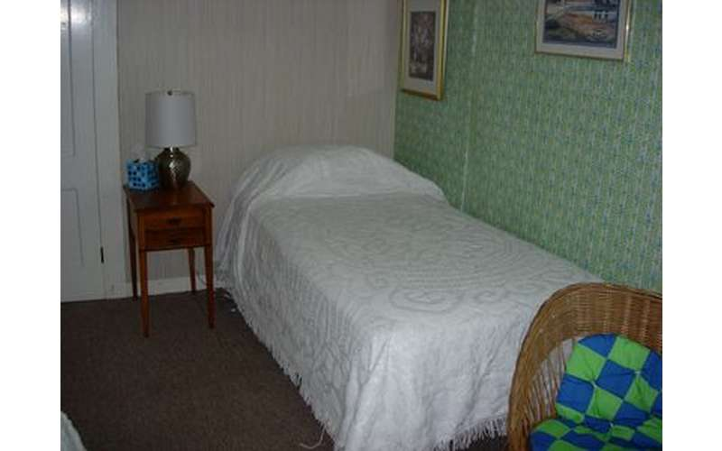a bed covered in white blankets next to a small lamp