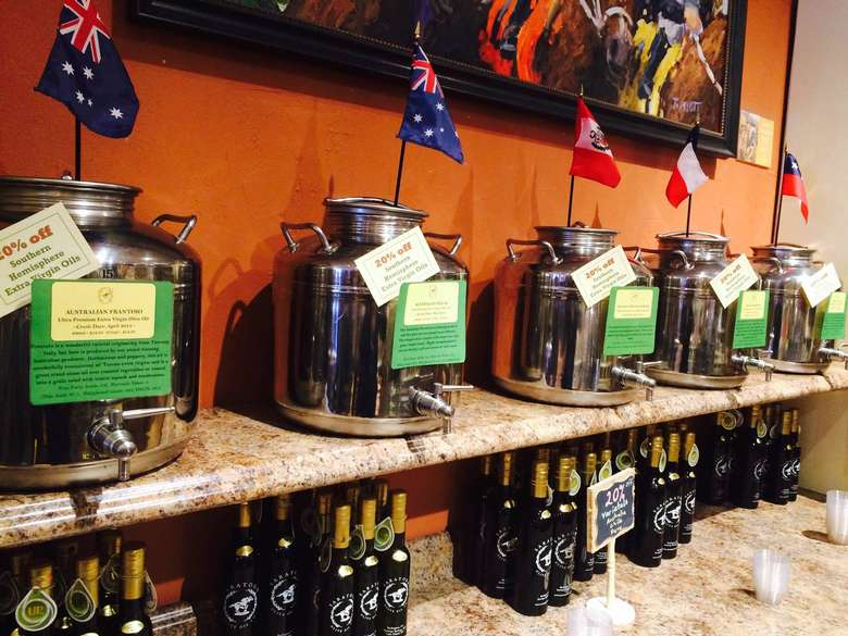 large olive oil dispensers with international flags on top of them and bottles of olive oil beneath them
