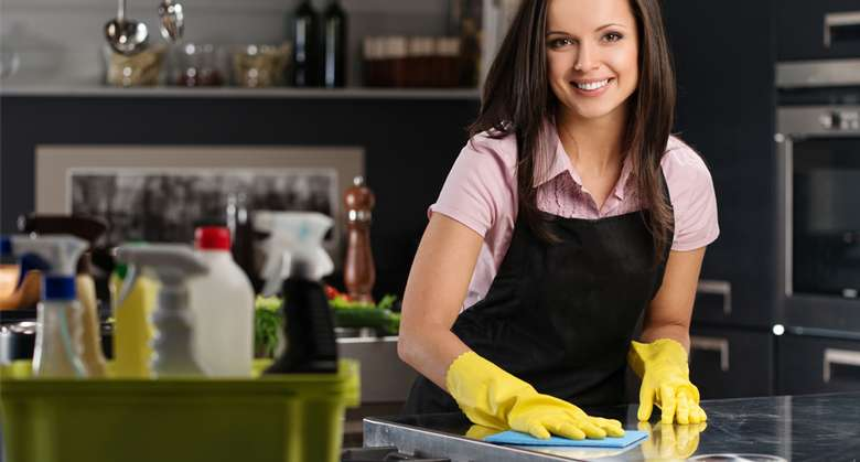 a woman with dish gloves cleaning a kitchen countertop