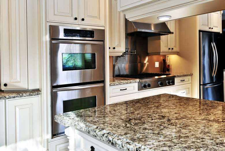 a kitchen with white cabinets, marble countertop