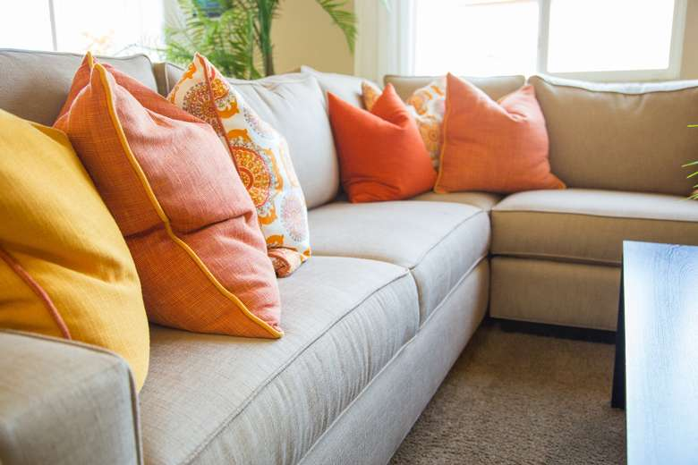 a beige couch with orange and yellow pillows