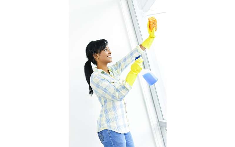 a woman with dish gloves cleaning a window