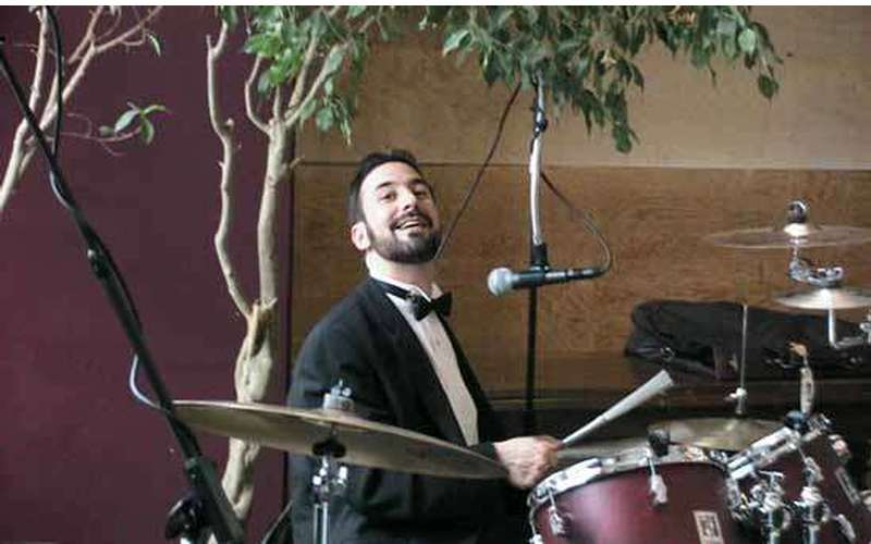 a man in a suit playing drums