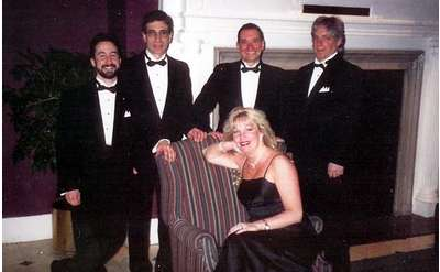 a group of four men and one woman dressed in professional attire