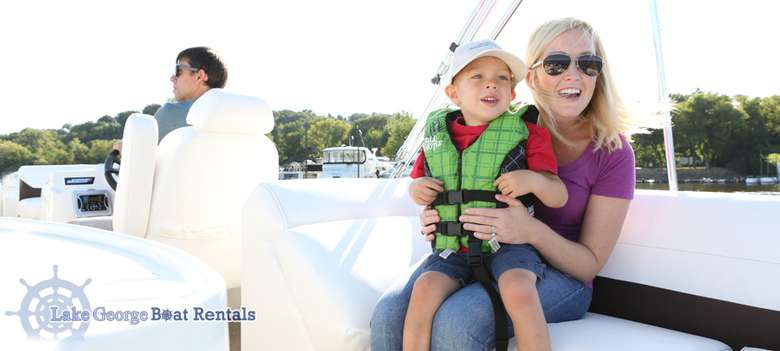 mom holding her son while her husband drives a boat