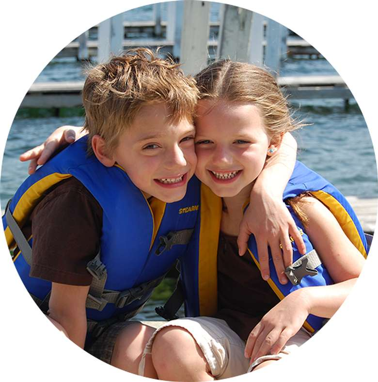two kids in life jackets smiling