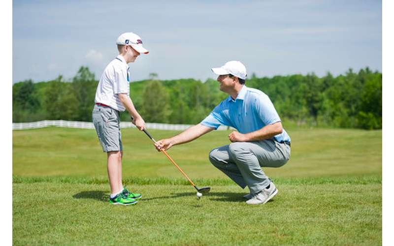 a man showing a little boy how to golf