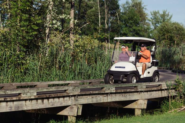 two men in golf cart driving over bridge