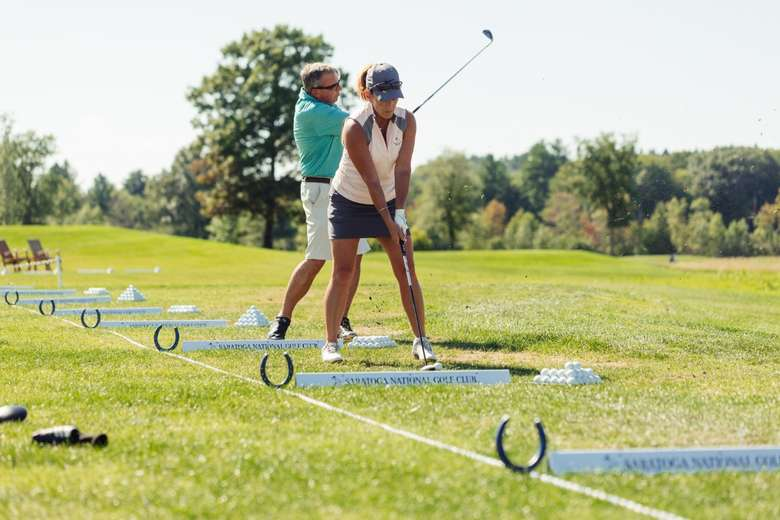 man and women hitting golf balls on the range