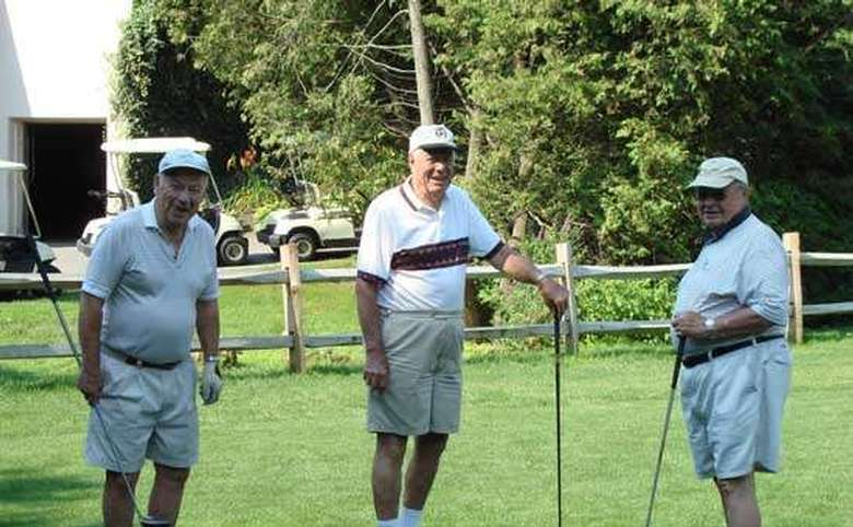 Three men wearing hats and holding golf clubs