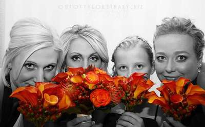 Girls in black and white looking out from behind bright orange flowers