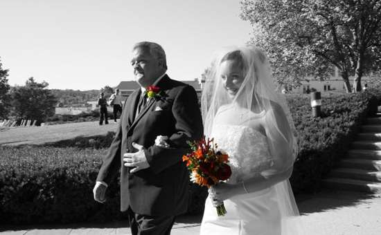 Woman and father walking down the aisle in black and white with bright orange and red bouquets