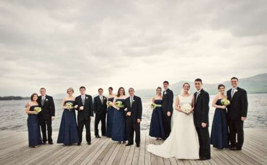 Wedding party standing on dark staggered in pairs