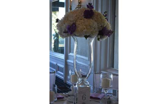 Flowers on top  of large glass vase
