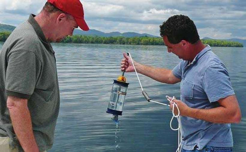 Two men examine a water quality sample