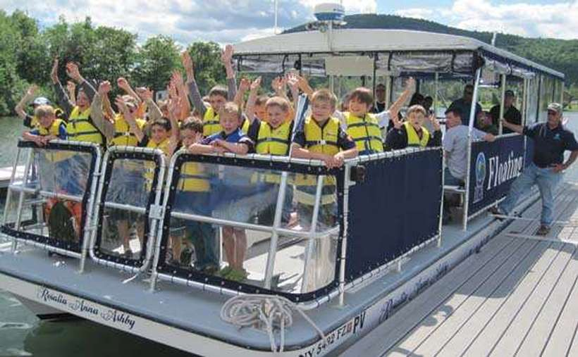 A group of kids in yellow life jackets on a boat