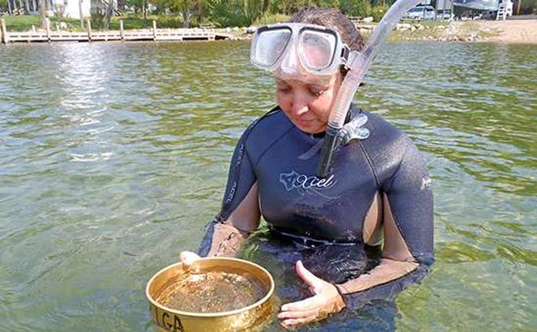 A woman in snorkeling gear checks a sample for signs of Asian clams