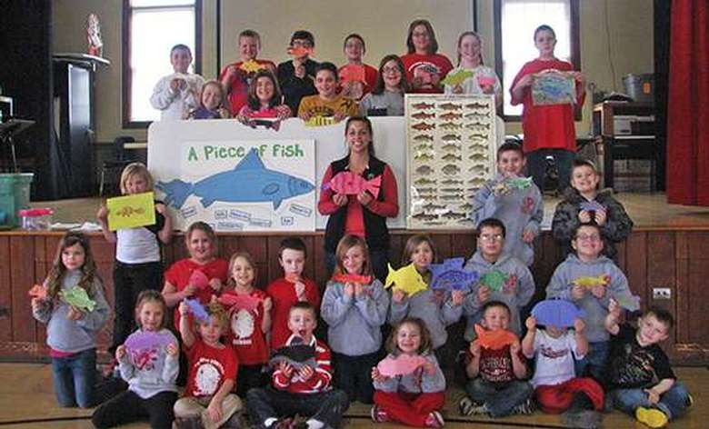 An instructor and a large group of kids showing off their fish crafts