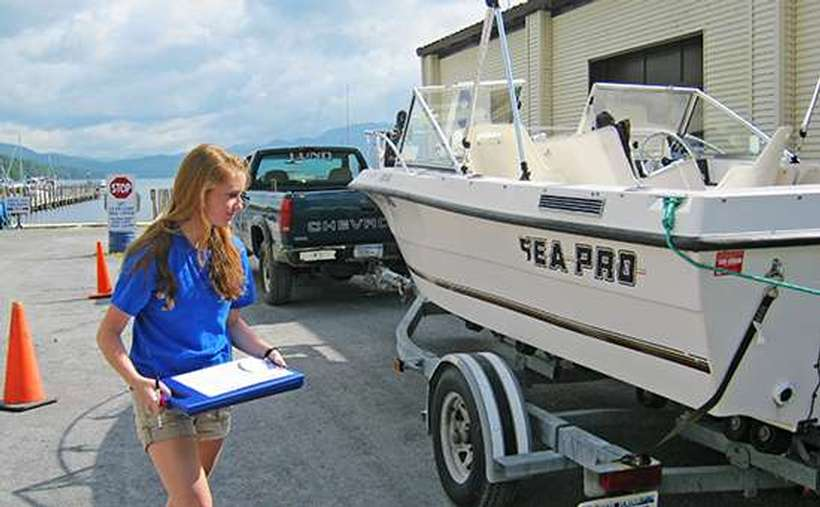 A young woman inspecting a boat before it can be launched into Lake George