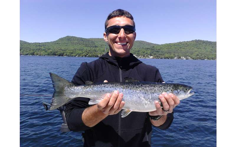 A man wearing sunglasses on a boat holding a fish