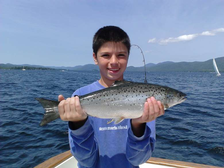 A boy on a boat holding a fish
