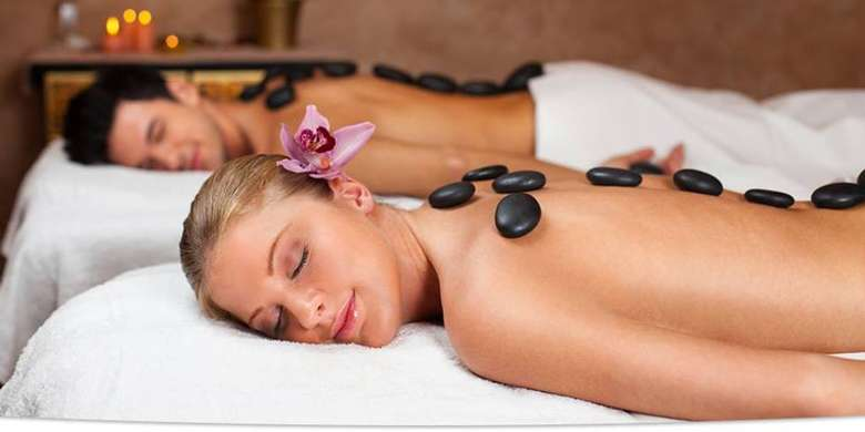 two people receiving hot stone massages
