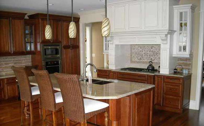 kitchen with white  and brown cabinets, an island, and a tiled backsplash
