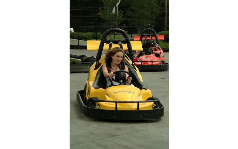 a young woman driving a go-kart