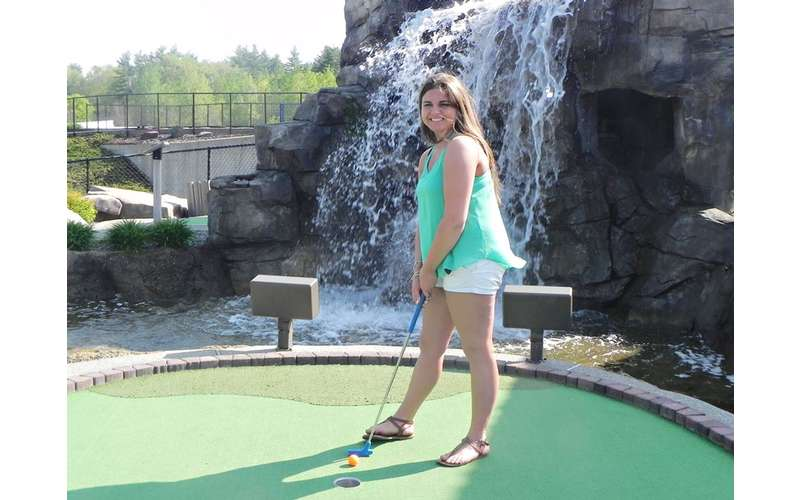 a young woman posing before hitting golf ball
